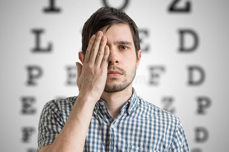Young man is covering his face with hand and checking his vision. Chart for eye sight testing in background.  stock images