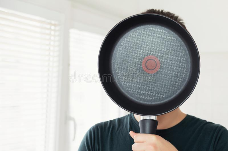 A young man covers his face with a frying pan. Photo taken at home kitchen stock photo