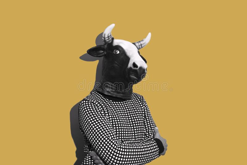Young man with a cow mask. Young caucasian man with a cow mask, in black and white, on a yellow background with some blank space on his both sides stock photography