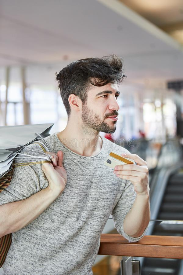 Young man with a credit card in retail. Shopping mall stock photography