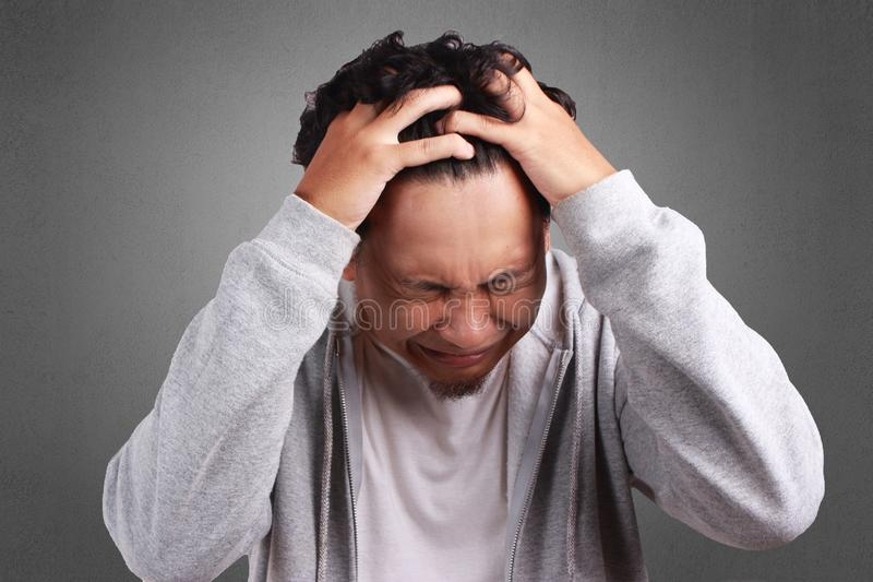 Young Man Cried, Stressed Expression. Young Asian man wearing white shirt and gray jacket cried, stressed expression. Background on gray. Close up head and royalty free stock photo