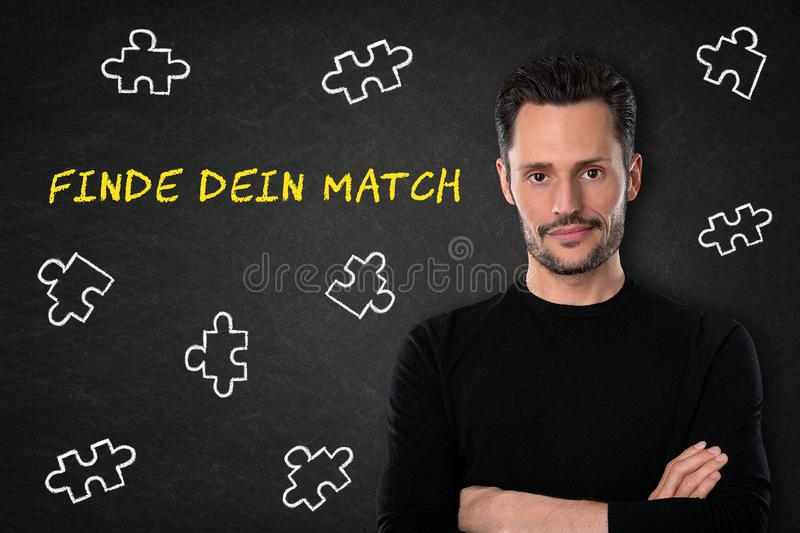 Young man with crossed arms, `Finde dein Match` text on a blackboard background. Translation: `Find your match` royalty free stock image