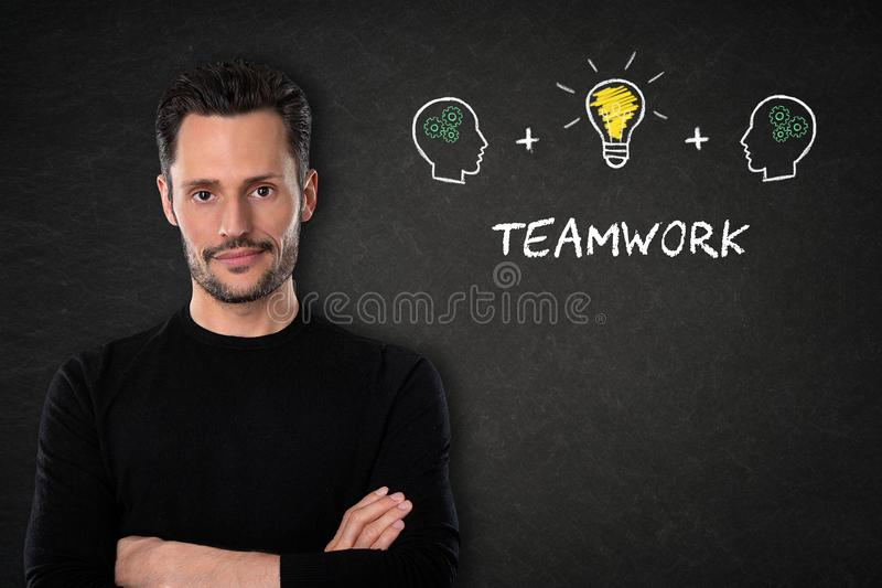 Young man with crossed arms, `Teamwork` text, heads and light bulb idea on a blackboard background. stock photo