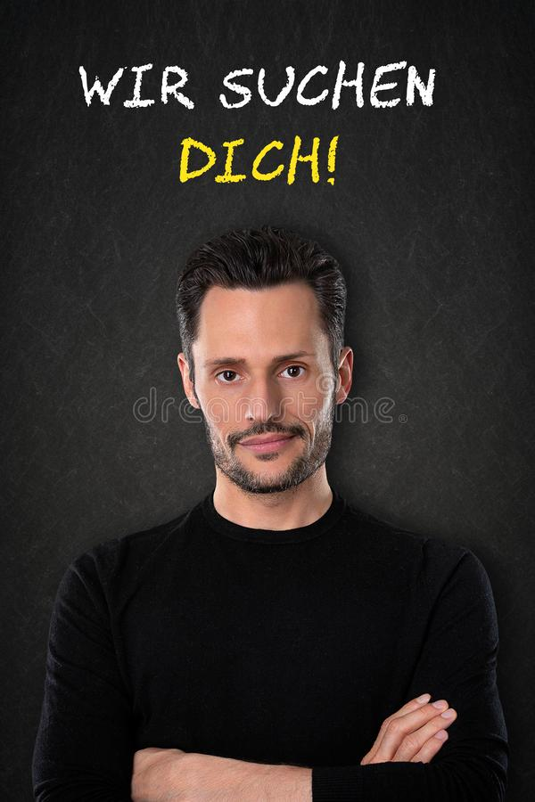 Young man with crossed arms and `Wir suchen dich` text on a blackboard background. Translation: `We are looking for you` royalty free stock photography