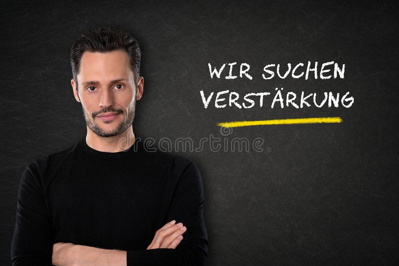 Young man with crossed arms and `Wir suchen dich` text on a blackboard background. Translation: `We are looking for you` vector illustration