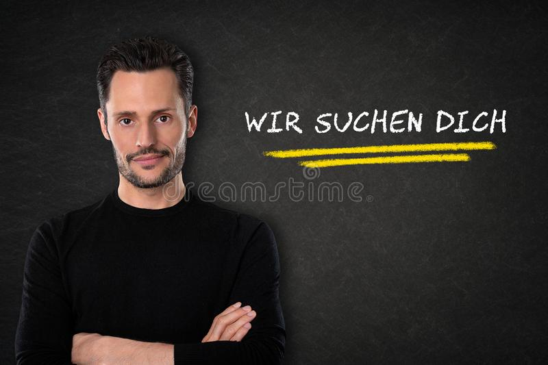 Young man with crossed arms, `Wir suchen dich` text on a blackboard background. Translation: `We are looking for you` royalty free stock images