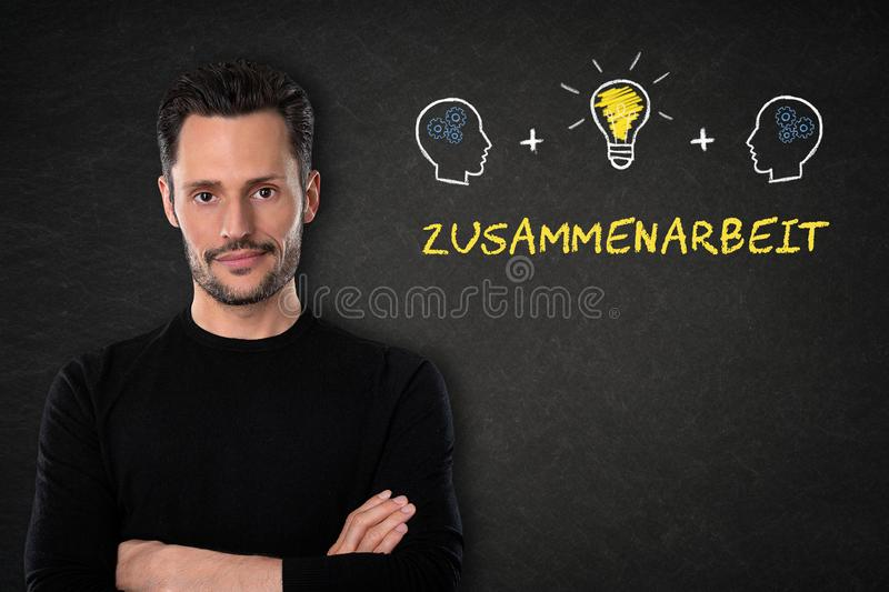 Young man with crossed arms, `Zusammenarbeit` text, heads, brain and light bulb on chalk board background. Translation: `Teamwork` stock photo