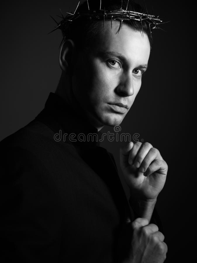Young man in crown of thorns, martyr and black suit jacket is ready to defend with clenched fists. Black-white picture. Young man in crown of thorns, martyr and royalty free stock photo