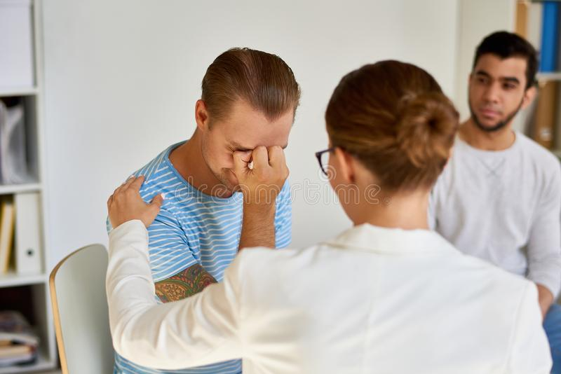 Young Man Crying During therapy Session. Portrait of modern young men crying while sharing trouble with female psychiatrist in group therapy session royalty free stock photo
