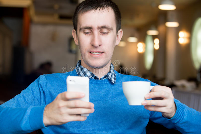 Young man with cup of coffee and smartphone stock image