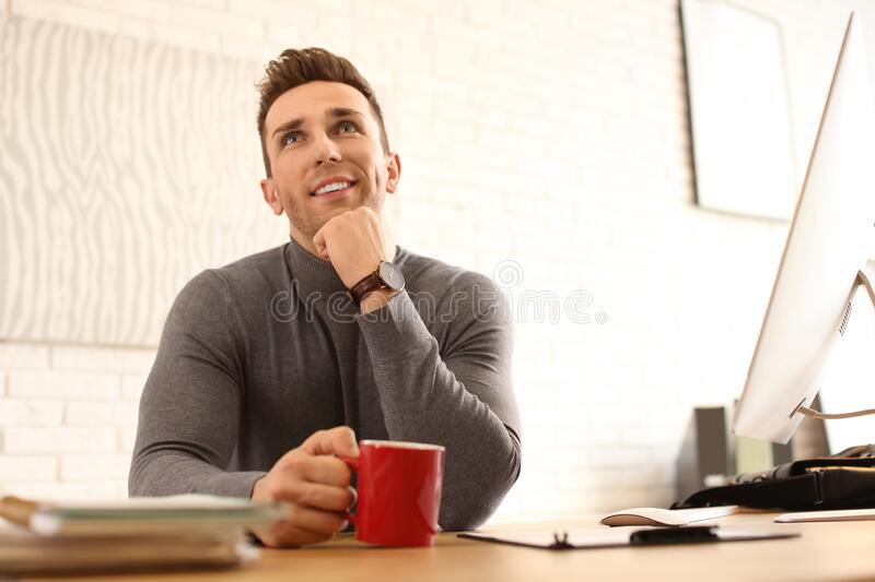 Young man with cup of drink relaxing at table in office. During break royalty free stock photography