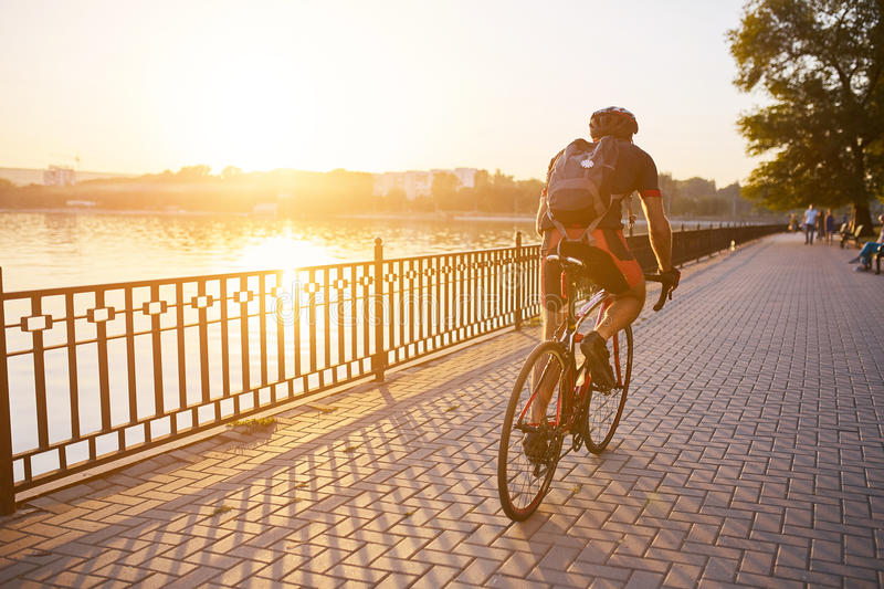 Young man are cycling road bike in the evening. Young man are cycling road bike by the lake in the park stock photo