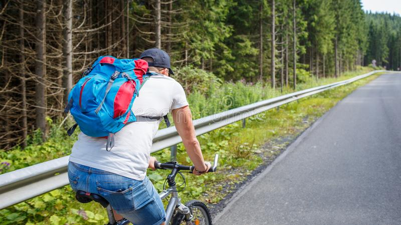 Young man cycling on road in mountains stock image