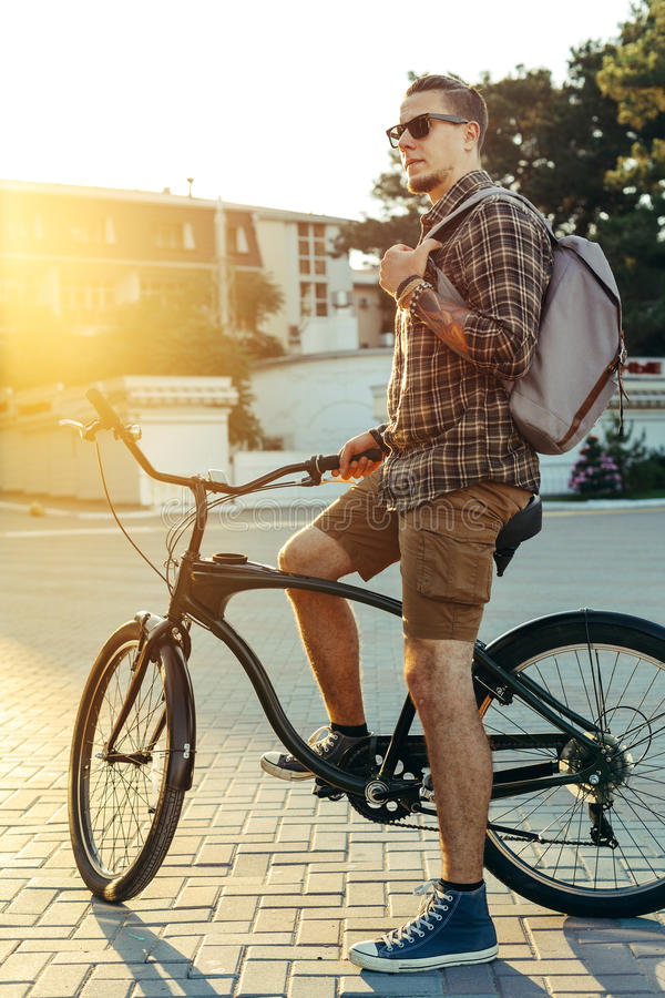 Young Man Cyclist With Bicycle Resting Daily Routine Lifestyle. Young male cyclist with a backpack in sun glasses resting while sitting on a bicycle against a stock image