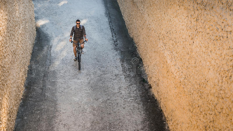 Young Man Cyclist Riding On Bike Down The Street, Top View. Daily Lifestyle Urban Resting Concept. Young Man Cyclist In Glasses With Backpack Riding On Bike Down stock photos
