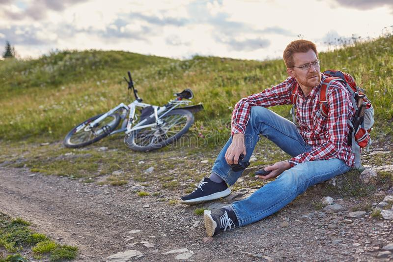 Young man cyclist sits on the edge of a dirt road royalty free stock photography