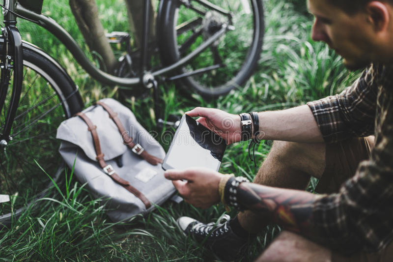 Young Man Cyclist Sits On Summer Meadow Near Bicycle, Holding And Looking At Tablet Recreation Resting Travel Destination Concept. Young fellow traveler cyclist royalty free stock photo