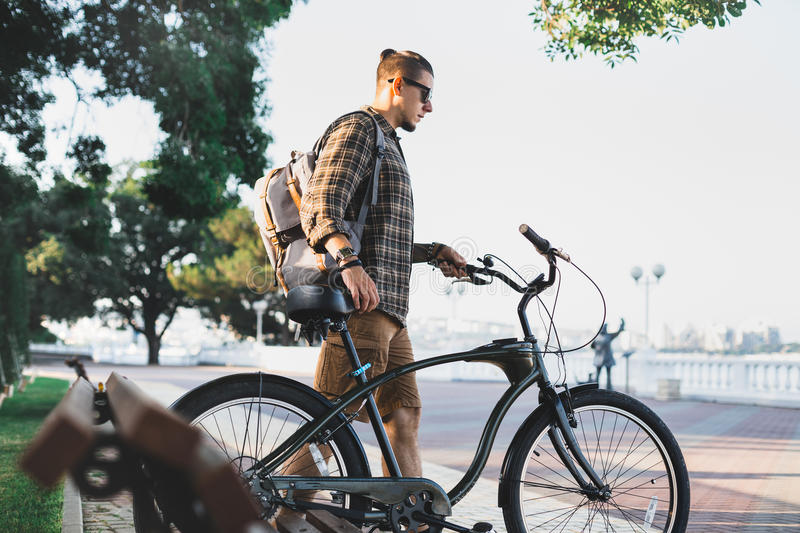 Young man cyclist walks with bicycles on embankment in summer Daily Lifestyle Urban Resting Concept. Young man cyclist with backpack walks with bicycles on royalty free stock photography