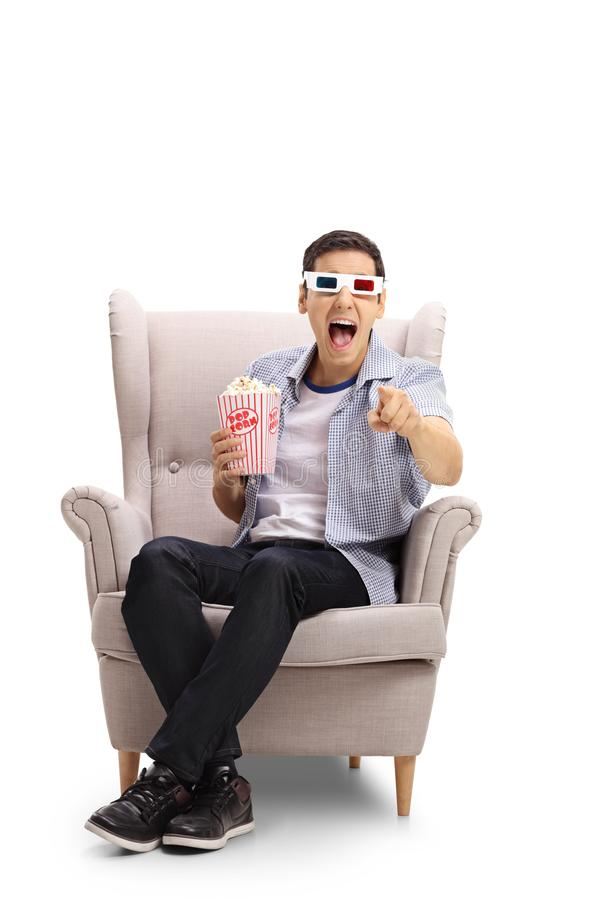 Young man with 3D glasses and popcorn seated in an armchair laughing and pointing at the camera royalty free stock photo