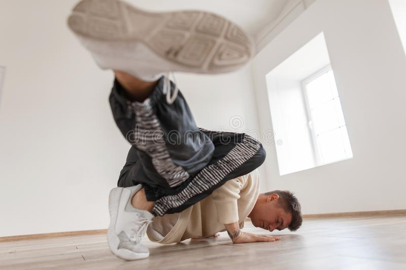 A young man is dancing break dance in a white pullover royalty free stock image