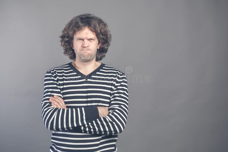 Young man with dark brown hair wears black and white striped casual tshirt looks angry, lips pursed frowning brows, isolated over royalty free stock image