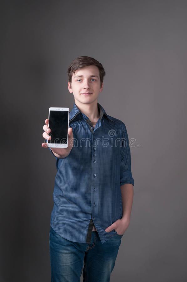 Young man with dark hair in blue shirt, holding hand in pocket, showing smartphone with blank screen. And looking at camera in front of gray background royalty free stock photos
