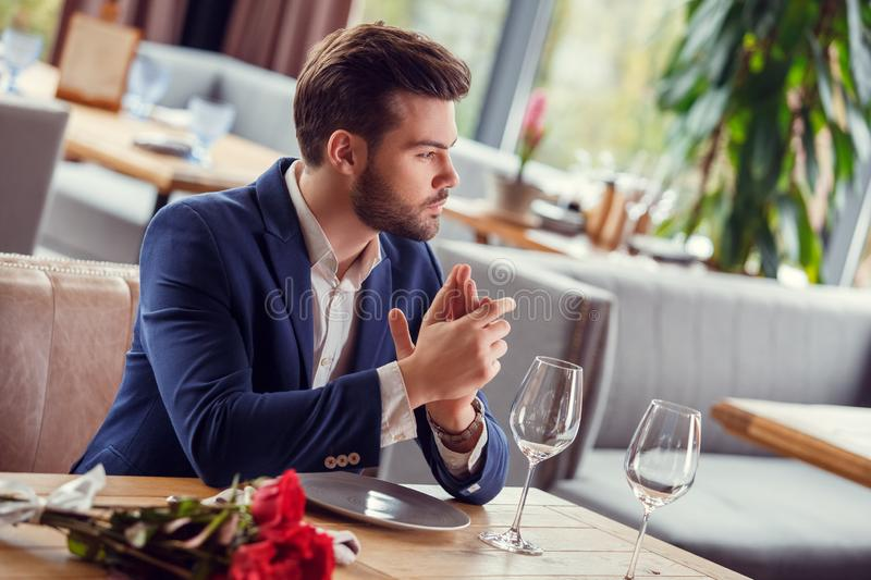 Young man on date in restaurant sitting with bouquet antici[ating girlfriend come excited royalty free stock photography