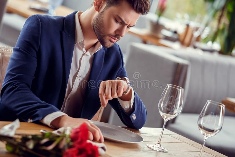 Young man on date in restaurant sitting with bouquet looking at watch waiting unsatisfied close-up stock photography