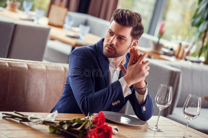 Young man on date in restaurant sitting with bouquet nervous stock photo