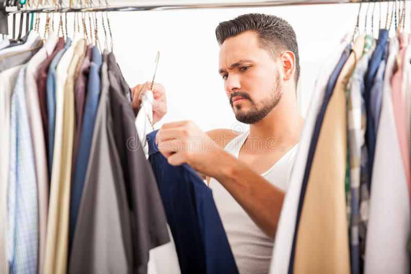 Young man deciding what clothes to wear. Good looking young man choosing between to shirts to wear while looking through his closet stock photo