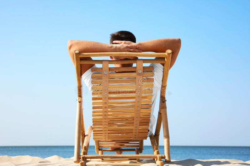 Young man  in deck chair on sandy beach stock photography