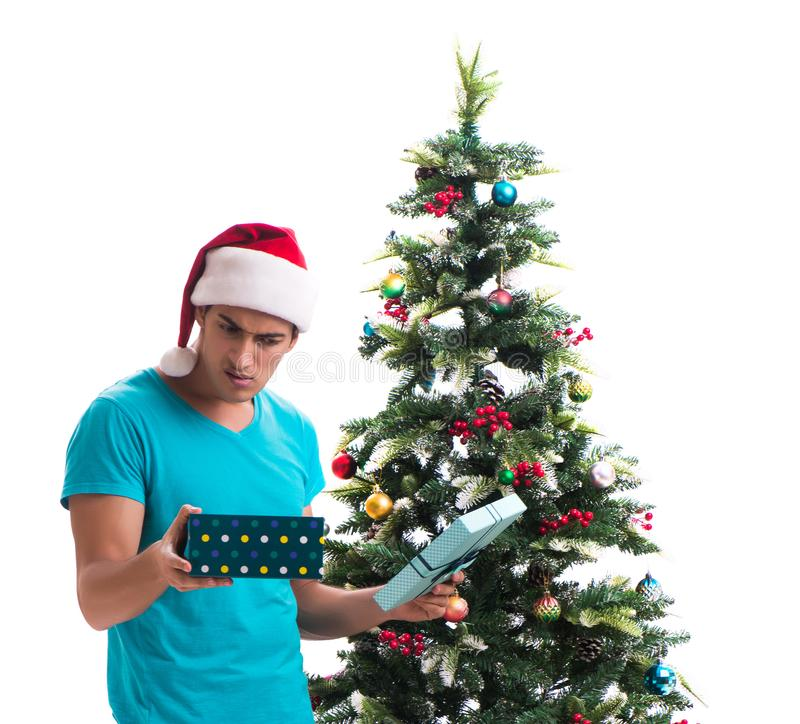 Young man decorating christmas tree isolated on white. The young man decorating christmas tree isolated on white stock image