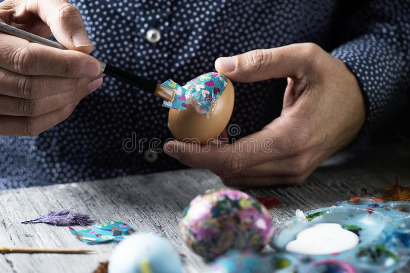 Young man decorating homemade easter eggs. Closeup of a young cacausian man decorating some homemade easter eggs by gluing some pieces of different papers, on a stock photography