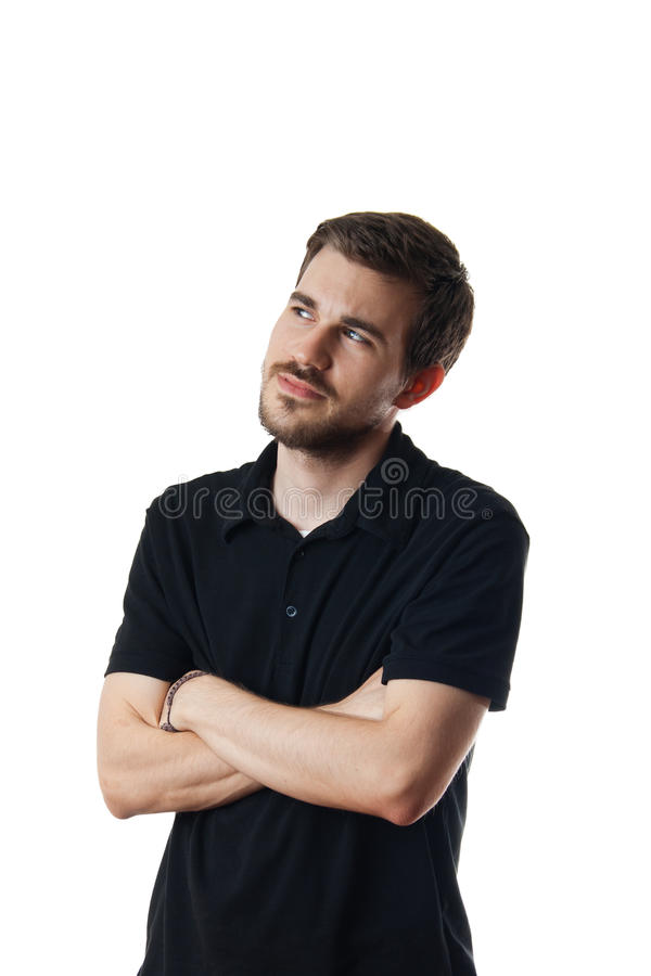 Young man deep in thought. Isolated on white image of a young man deep in thought, as he stands arms folded looking off into the distance royalty free stock photo