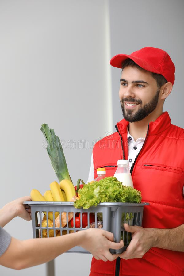Young man delivering food to customer. Indoors stock photos