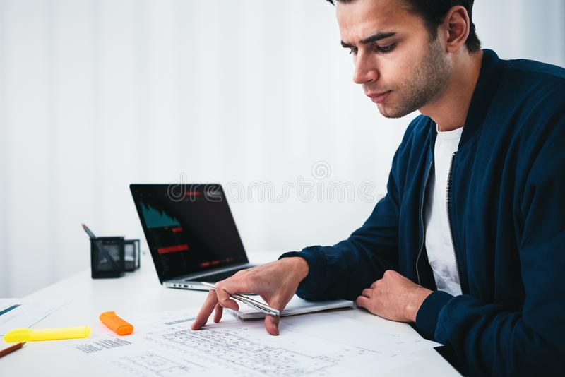 Young man designer sketching a construction project at notebook and drawing plan while working at office stock photo