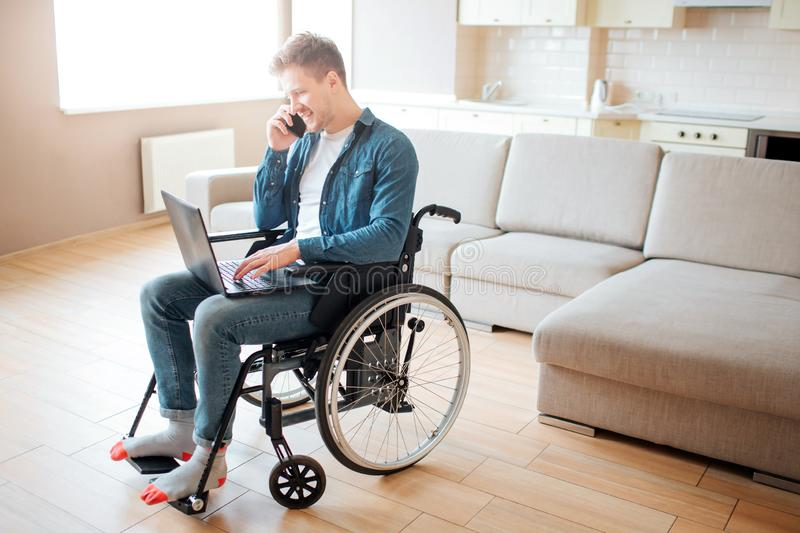 Young man with disability sitting on wheelchair. Working on laptop and talking on phone. Alone in big room with daylight stock photography