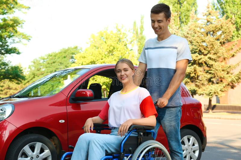 Young man with  woman in wheelchair near car outdoors royalty free stock image