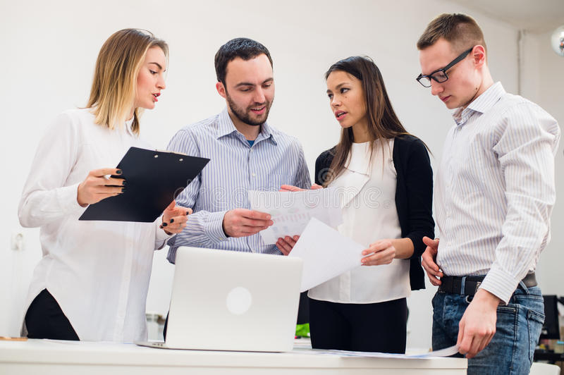 Young man discussing market research with colleagues in a meeting. Team of professionals having conversation at. Young men discussing market research with royalty free stock image
