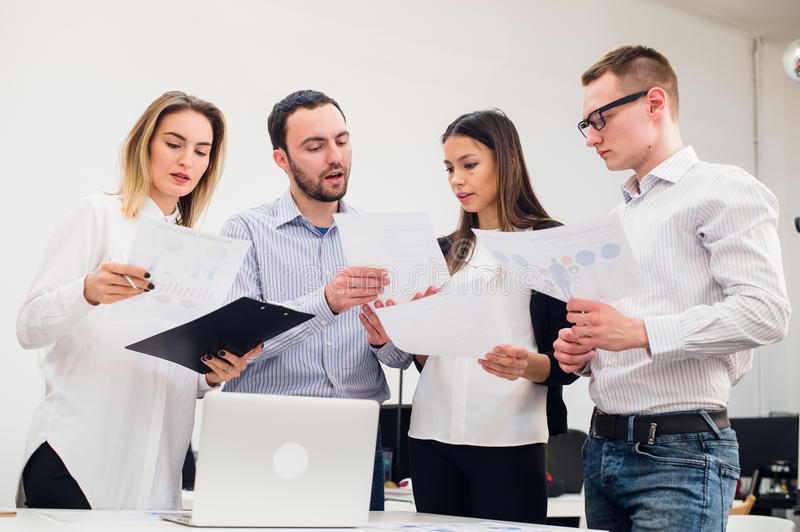 Young man discussing market research with colleagues in a meeting. Team of professionals having conversation at. Young men discussing market research with royalty free stock photo