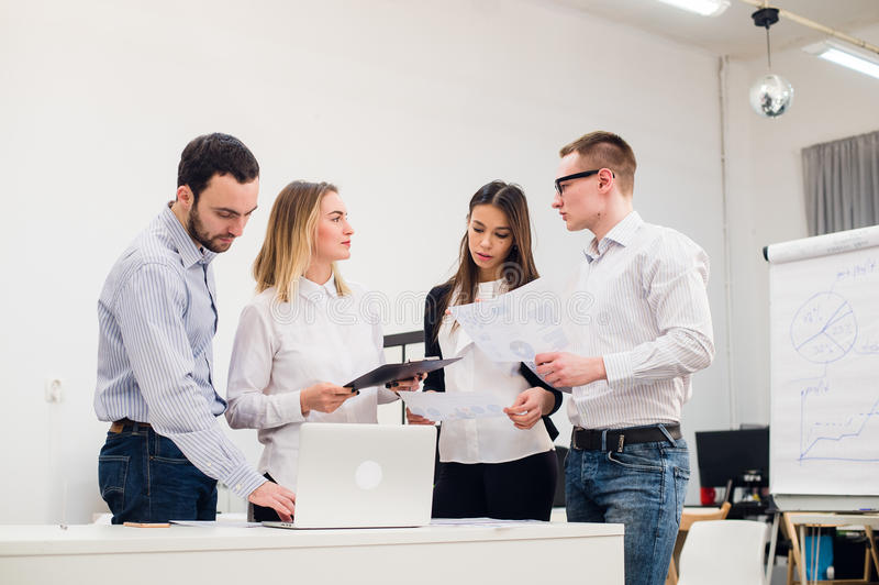 Young man discussing market research with colleagues in a meeting. Team of professionals having conversation at. Young men discussing market research with stock photography