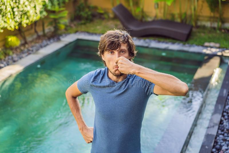 Young man with disgust on his face pinches nose, something stinks, very bad smell in swimming pool because of pool royalty free stock photography