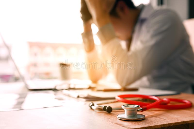 Young man doctor being exhausted in the office room. Young man doctor being exhausted in the office room royalty free stock photos