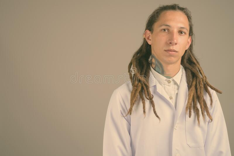 Young man doctor with dreadlocks against gray background stock photos
