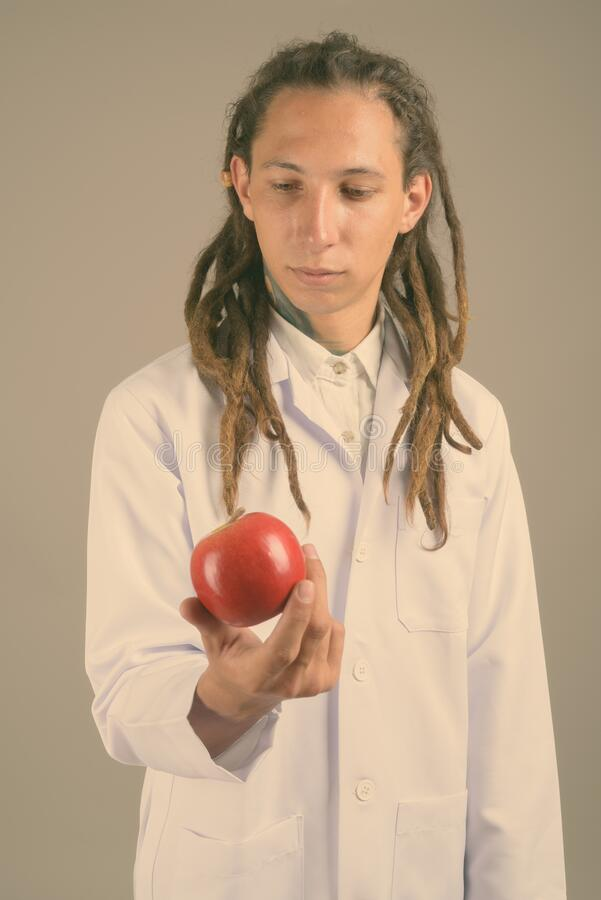 Young man doctor with dreadlocks against gray background stock photography