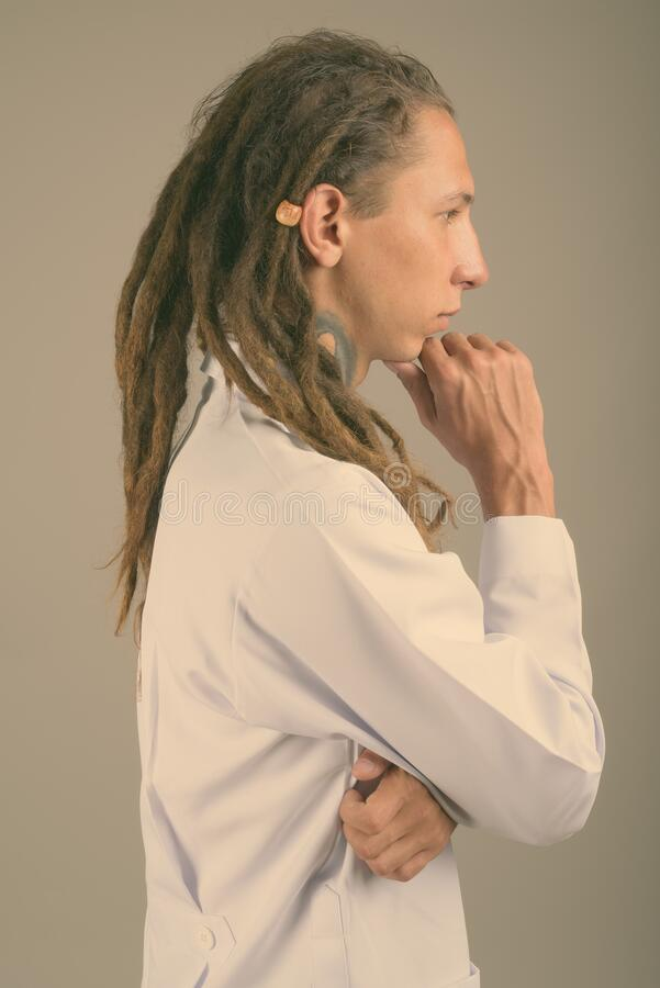 Young man doctor with dreadlocks against gray background stock images