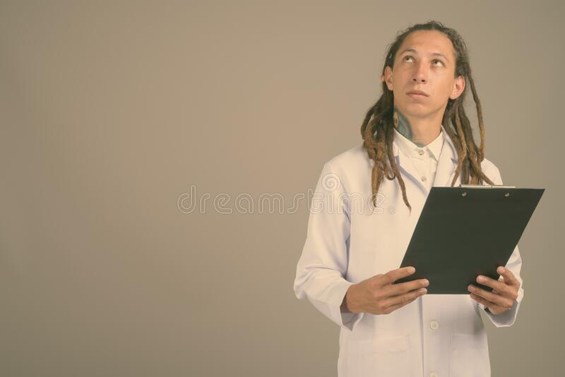 Young man doctor with dreadlocks against gray background stock image