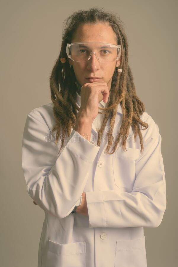 Young man doctor with dreadlocks wearing protective glasses against gray background stock images
