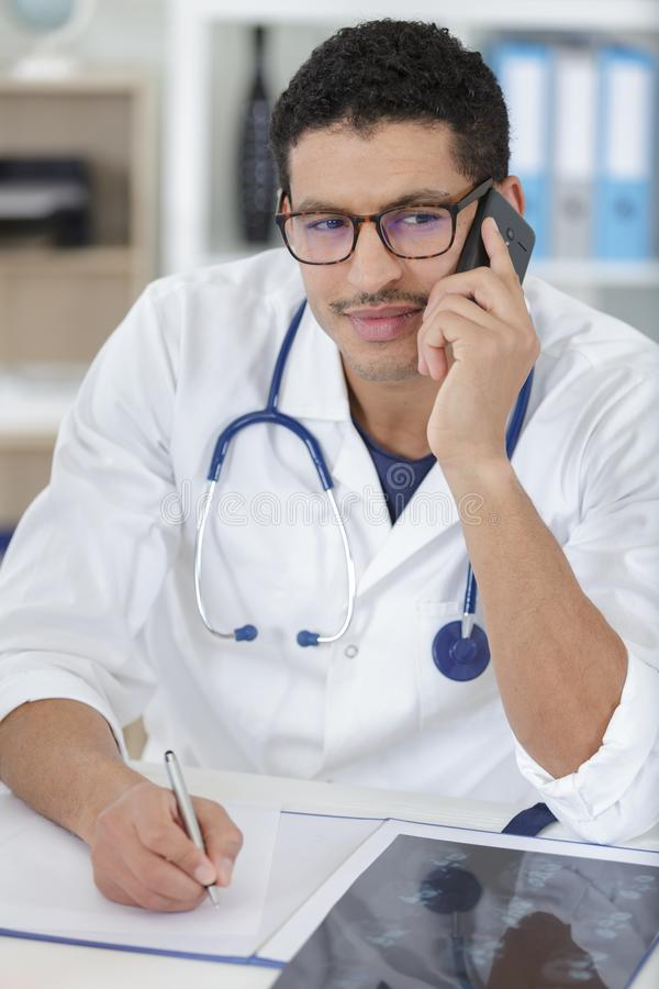 Young man doctor on phone. Young man doctor is on the phone royalty free stock photo