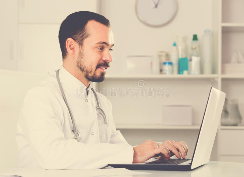 Young man doctor ready to receive clients royalty free stock photos